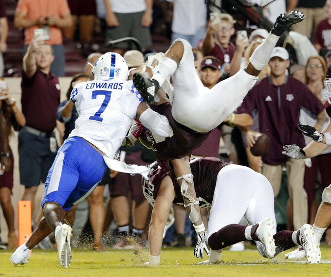 Texas A&M running back Trayveon Williams (5) dives over tight end Trevor Wood (80) to score and win an NCAA college football game as Kentucky safety Mike Edwards (7) defends in overtime of an NCAA college football game Saturday, Oct. 6, 2018, in College Station, Texas. (AP Photo/Michael Wyke)