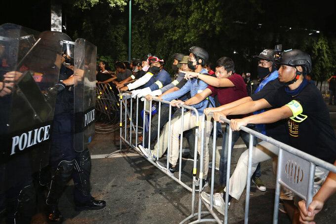 Pro-democracy protesters stand in front of Thai policemen with riot shields during a demonstration in Bangkok, Thailand, Thursday, Oct. 15, 2020. Thai police dispersed a group of protesters holding an overnight rally outside the prime minister's office. (AP Photo/Rapeephat Sitichailapa)