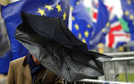 A man shelters with an umbrella as he walks by Pro EU protestors  holding flags opposite the Houses of Parliament in London, Thursday, April 4, 2019.  The British government and senior opposition figures were meeting Thursday in search of a new plan on how the country leaves the European Union as Prime Minister Theresa May tried to stop her shift toward compromise from splitting her Conservative Party. (AP Photo/Frank Augstein)