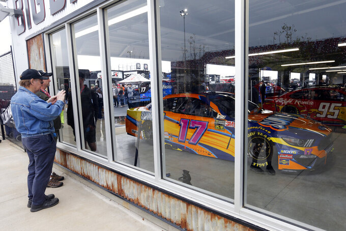 Fans take pictures at the new garage facilities before the 1000Bulbs.com 500 at Talladega Superspeedway, Sunday, Oct 13, 2019, in Talladega, Ala. (AP Photo/Butch Dill)