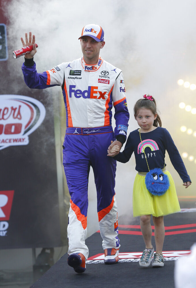 Denny Hamlin and his daughter Jordan, wave to the crowd during driver introductions prior to the start of the NASCAR Cup series auto race at Richmond Raceway in Richmond, Va., Saturday, April 13, 2019. (AP Photo/Steve Helber)