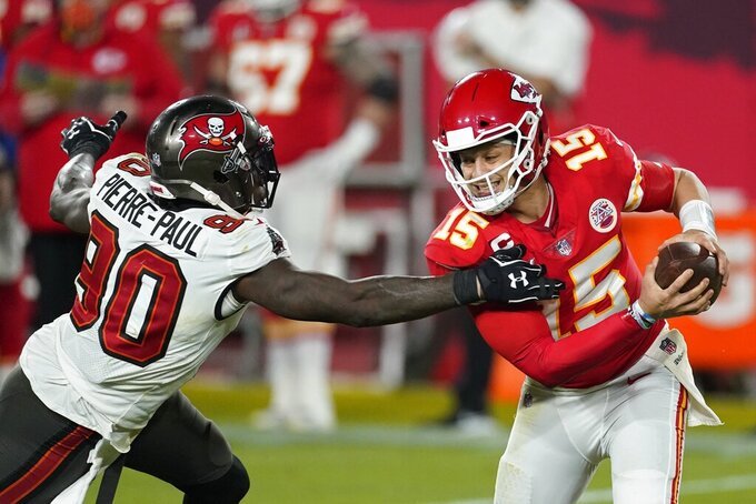 Kansas City Chiefs quarterback Patrick Mahomes escapes a tackle by Tampa Bay Buccaneers outside linebacker Jason Pierre-Paul during the second half of the NFL Super Bowl 55 football game Sunday, Feb. 7, 2021, in Tampa, Fla. (AP Photo/Ashley Landis)