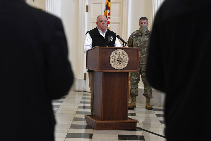 Maryland Gov. Larry Hogan speaks during a news conference in Annapolis, Md., Friday, April 10, 2020. Hogan provided updates on the state's response to the coronavirus pandemic, including key budget actions and efforts to bolster the process to apply for unemployment. Adjutant General Major Gen. Timothy Gowen listens at right. (AP Photo/Susan Walsh)