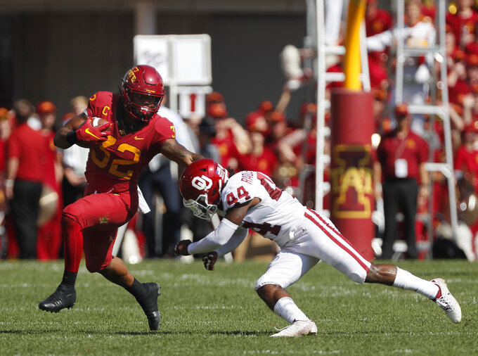 Iowa State running back David Montgomery, left, runs the ball as he slips away from Oklahoma defensive back Brendan Radley-Hiles, right, during the first half of an NCAA college football game, Saturday, Sept. 15, 2018, in Ames, Iowa. (AP Photo/Matthew Putney)