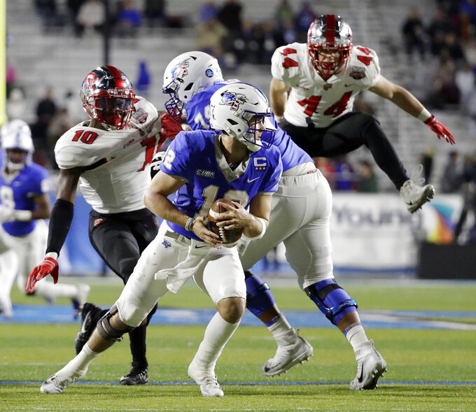 Middle Tennessee quarterback Brent Stockstill (12) scrambles away from Western Kentucky defensive lineman DeAngelo Malone (10) and linebacker Ben Holt (44) in the first half of an NCAA college football game Friday, Nov. 2, 2018, in Murfreesboro, Tenn. (AP Photo/Mark Humphrey)