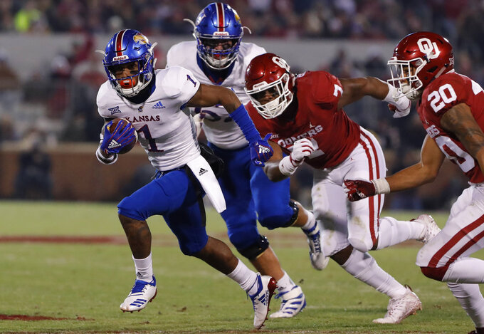 Kansas running back Pooka Williams Jr. (1) runs ahead of Oklahoma defenders during the first half of an NCAA college football game in Norman, Okla., Saturday, Nov. 17, 2018. (AP Photo/Alonzo Adams)