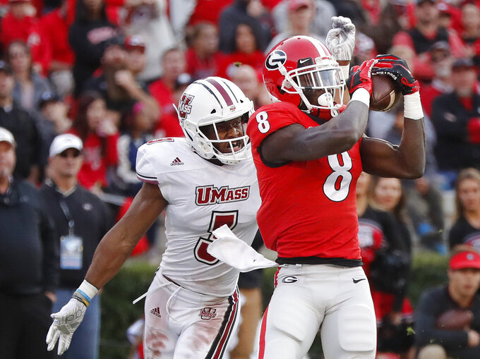 Georgia wide receiver Riley Ridley (8) makes a catch for a touchdown as Massachusetts cornerback Lee Moses (3) defends during the first half of an NCAA college football game Saturday, Nov. 17, 2018, in Athens, Ga. (AP Photo/John Bazemore)