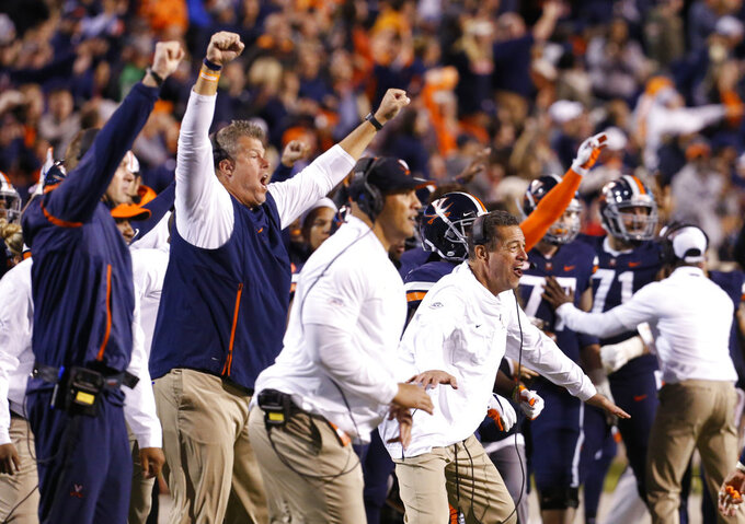 Members of the Virginia coaching staff celebrate a play during the second half of an NCAA college football game in Charlottesville, Va., Saturday, Oct. 13, 2018. Virginia defeated Miami 16-13. (AP Photo/Steve Helber)