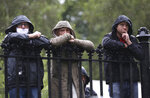Three men watch from the railings in the rain as attendees arrive for the former Northern Ireland lawmaker and Nobel Peace Prize winner John Hume's funeral Mass at St Eugene's Cathedral in Londonderry, Northern Ireland, Wednesday, Aug. 5, 2020. Hume was co-recipient of the 1998 Nobel Peace Prize with fellow Northern Ireland lawmaker David Trimble, for his work in the Peace Process in Northern Ireland. (AP Photo/Peter Morrison)