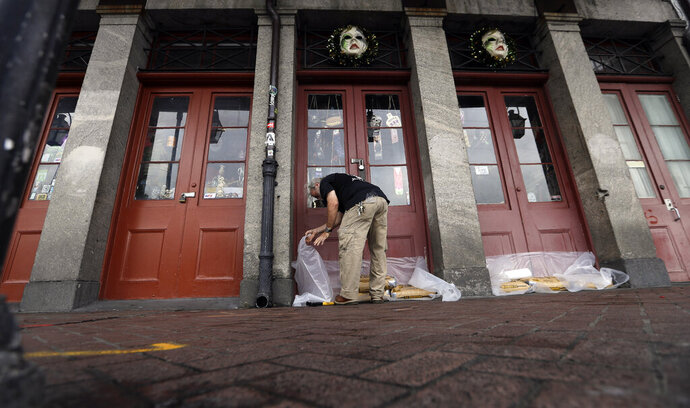 FILE - In this July 12, 2019, file photo Jake Summers puts concrete bags in front of a business in the French Quarter in New Orleans, ahead of Tropical Storm Barry. With earthquakes in California and Hurricane Barry striking states along the Gulf of Mexico and in the Midwest, small business owners should look at their insurance policies and determine how well covered they'd be in the event of a natural disaster. (AP Photo/David J. Phillip, File)
