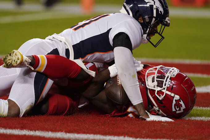 Kansas City Chiefs wide receiver Tyreek Hill (10) tries to catch a pass as Denver Broncos cornerback A.J. Bouye (21) defends in the first half of an NFL football game in Kansas City, Mo., Sunday, Dec. 6, 2020. The pass was called incomplete but replays showed the ball never hit the ground. (AP Photo/Charlie Riedel)