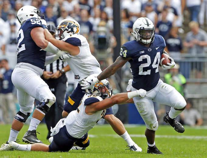 Penn State's Miles Sanders (24) gets past Kent State's Dalton Hicks (32) during the first half of an NCAA college football game in State College, Pa., Saturday, Sept. 15, 2018. (AP Photo/Chris Knight)
