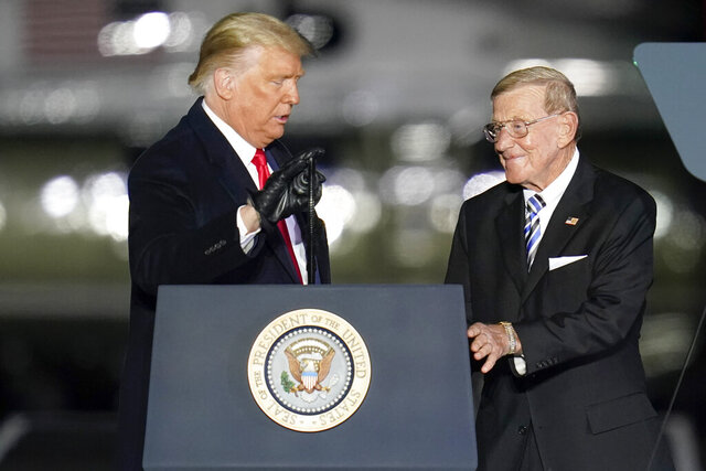 "FILE - In this Oct. 31, 2020, file photo, President Donald Trump, left, introduces former college football coach Lou Holtz during a campaign stop in Butler, Pa. Holtz has tested positive for the coronavirus. The 83-year-old former college football coach confirmed the test Thursday, Nov. 19, 2020, to Columbia, S.C., TV station WOLO. ""I don't have a lot of energy right now,"" Holtz told the ABC station. (AP Photo/Keith Srakocic, File)"