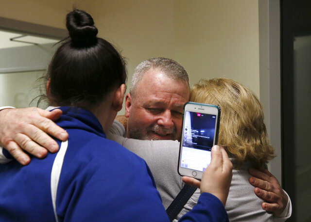 Ricky Davis, center, is hugged by his mother, Maureen Klein, right, after he was released from custody at the El Dorado County Jail in Placerville, Calif., Thursday, Feb. 13, 2020. Davis spent about 15 years in prison after being wrongly convicted of second-degree murder in the stabbing death of his housemate, a newspaper columnist, in 2004. The conviction was thrown out after new evidence was found implicating another person. (AP Photo/Rich Pedroncelli)