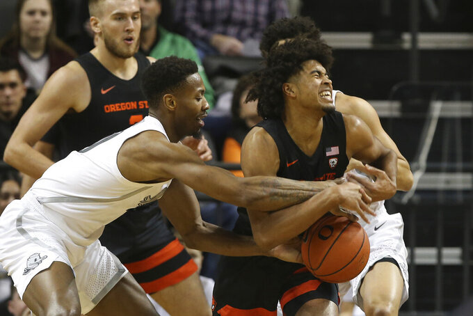 Oregon State's Ethan Thompson, right, reacts to pressure from Oregon's Shakur Juiston, left, with Oregon State's Tres Tinkle, left rear, and Oregon's Will Richardson, right rear, nearby during the first half of a NCAA college basketball game in Eugene, Ore., Thursday, Feb. 27, 2020. (AP Photo/Chris Pietsch)