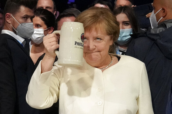German chancellor Angela Merkel salutes with a beer mug during a state election campaign in Munich, Germany, Friday, Sept. 24, 2021 two days before the General election on Sunday, Sept. 26, 2021. (AP Photo/Matthias Schrader)