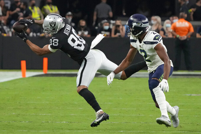 Las Vegas Raiders wide receiver Marcell Ateman (88) reaches out to try and catch a pass against Seattle Seahawks cornerback Ahkello Witherspoon (2) during the first half of an NFL preseason football game, Saturday, Aug. 14, 2021, in Las Vegas. (AP Photo/Rick Scuteri)