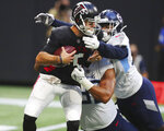 Atlanta Falcons quarterback AJ McCarron, left, is sacked by Tennessee Titans defensive tackle Trevon Coley and outside linebacker Rashad Weaver during the first half of an NFL football preseason game Friday, Aug. 13, 2021, in Atlanta. (Curtis Compton/Atlanta Journal-Constitution via AP)