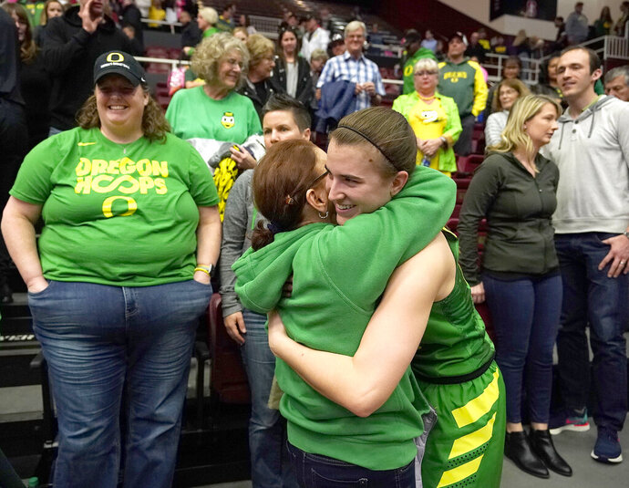 Oregon guard Sabrina Ionescu, front right, is hugged by a family member after a victory over Stanford in an NCAA college basketball game Sunday, Feb. 10, 2019, in Stanford, Calif. (AP Photo/Tony Avelar)