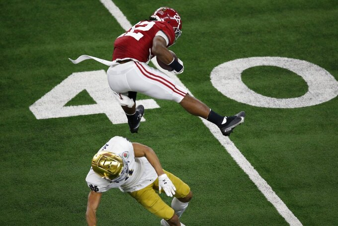 Alabama running back Najee Harris (22) hurdles Notre Dame cornerback Nick McCloud (4) as he carries the ball for a long gain in the first half of the Rose Bowl NCAA college football game in Arlington, Texas, Friday, Jan. 1, 2021. (AP Photo/Roger Steinman)