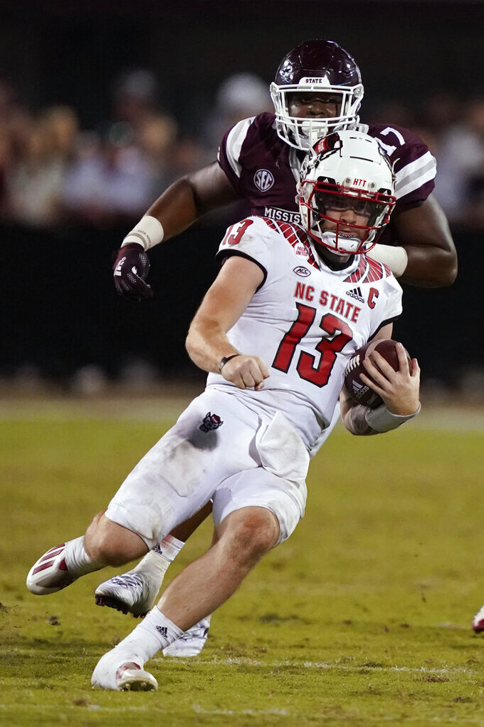 North Carolina State quarterback Devin Leary (13) slides as a Mississippi State defender closes in during the second half of an NCAA college football game in Starkville, Miss., Saturday, Sept. 11, 2021. (AP Photo/Rogelio V. Solis)