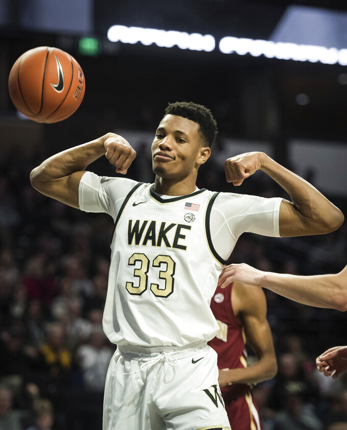 Wake Forest freshman forward Ody Oguama (33) flexes his biceps after scoring a basket over Boston College in the first half of an ACC college basketball game on Sunday, Jan. 19, 2020, at Joel Coliseum in Winston-Salem, N.C. (Allison Lee Isley/Winston-Salem Journal via AP)