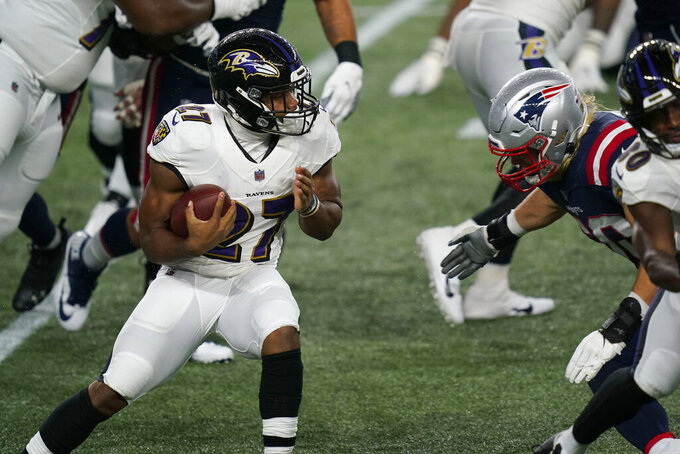 Baltimore Ravens running back J.K. Dobbins, left, carries the ball as New England Patriots defensive lineman Chase Winovich, right, closes in for a tackle in the first half of an NFL football game, Sunday, Nov. 15, 2020, in Foxborough, Mass. (AP Photo/Elise Amendola)