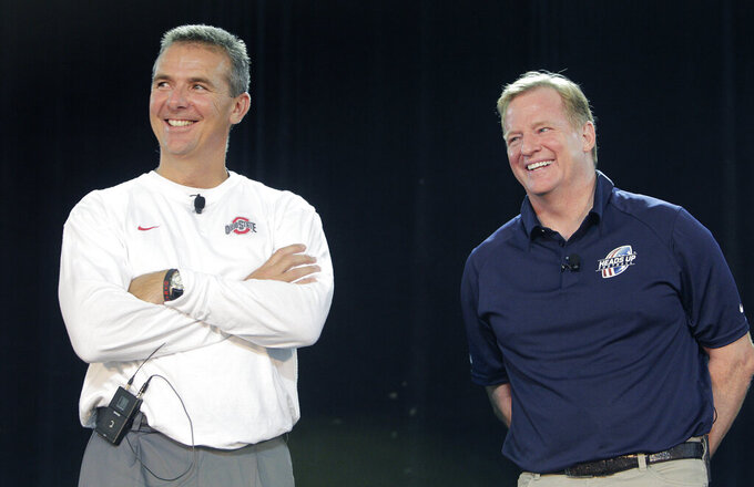 FILE - NFL Commissioner Roger Goodell, right, and Ohio State NCAA college football head coach Urban Meyer answer questions during a safety clinic for mothers of youth football players in Columbus, Ohio, in this Thursday, Aug. 1, 2013, file photo. A person familiar with the search says Urban Meyer and the Jacksonville Jaguars are working toward finalizing a deal to make him the team's next head coach. The person spoke to The Associated Press on the condition of anonymity Thursday, Jan. 14, 2021, because a formal agreement was not yet in place. (AP Photo/Jay LaPrete, File)