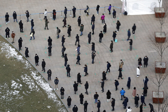 People queue in line to wait for coronavirus testing while maintaining social distancing at Seoul Plaza in Seoul, South Korea, Friday, Dec. 18, 2020. (AP Photo/Lee Jin-man)