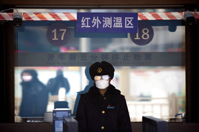 A station worker wears a face mask and goggles as she waits to check passengers' tickets at the Beijing Railway Station in Beijing, Saturday, Feb. 15, 2020. People returning to Beijing will now have to isolate themselves either at home or in a concentrated area for medical observation, said a notice from the Chinese capital's prevention and control work group published by state media late Friday. (AP Photo/Mark Schiefelbein)