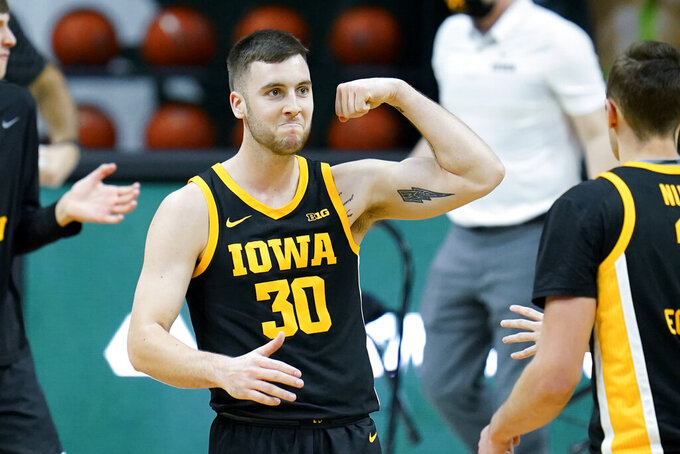 Iowa guard Connor McCaffery (30) flexes his muscle in the second half of an NCAA college basketball game against Michigan State in East Lansing, Mich., Saturday, Feb. 13, 2021. (AP Photo/Paul Sancya)