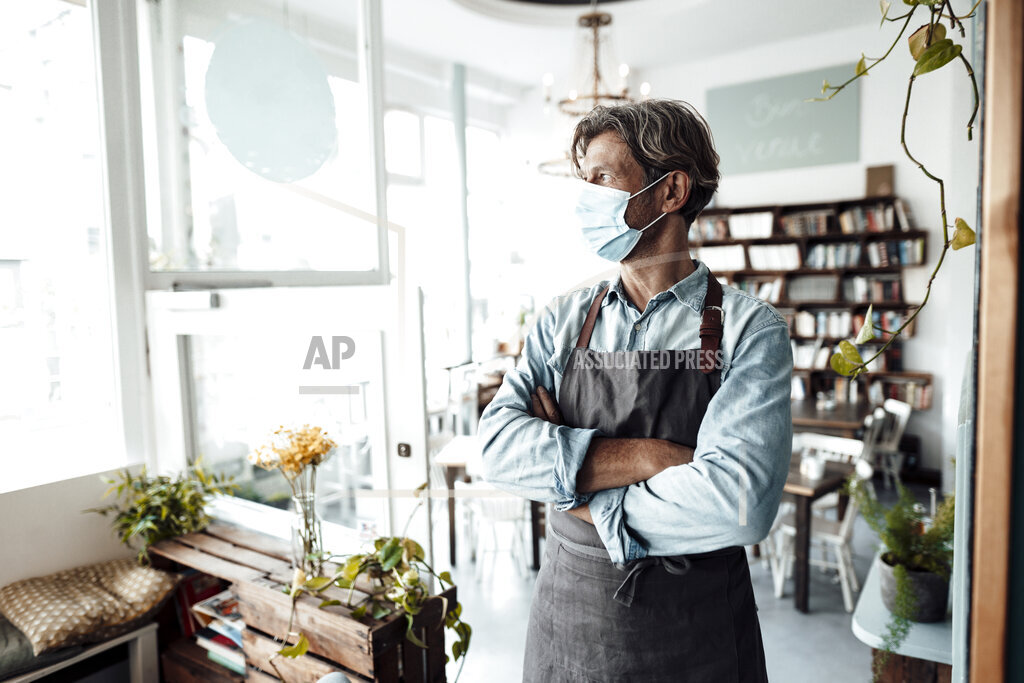 Male cafe owner standing with arms crossed in cafe during pandemic
