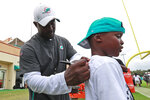 Miami Dolphins head coach Brian Flores, left, signs an autograph after the teams NFL football training camp, Monday, Aug. 5, 2019 in Davie, Fla. The Dolphins allowed a franchise record 6,257 yards in 2018, and new coach Brian Flores has brought to Miami a scheme that redefines the meanings of positions. (AP Photo/Wilfredo Lee)