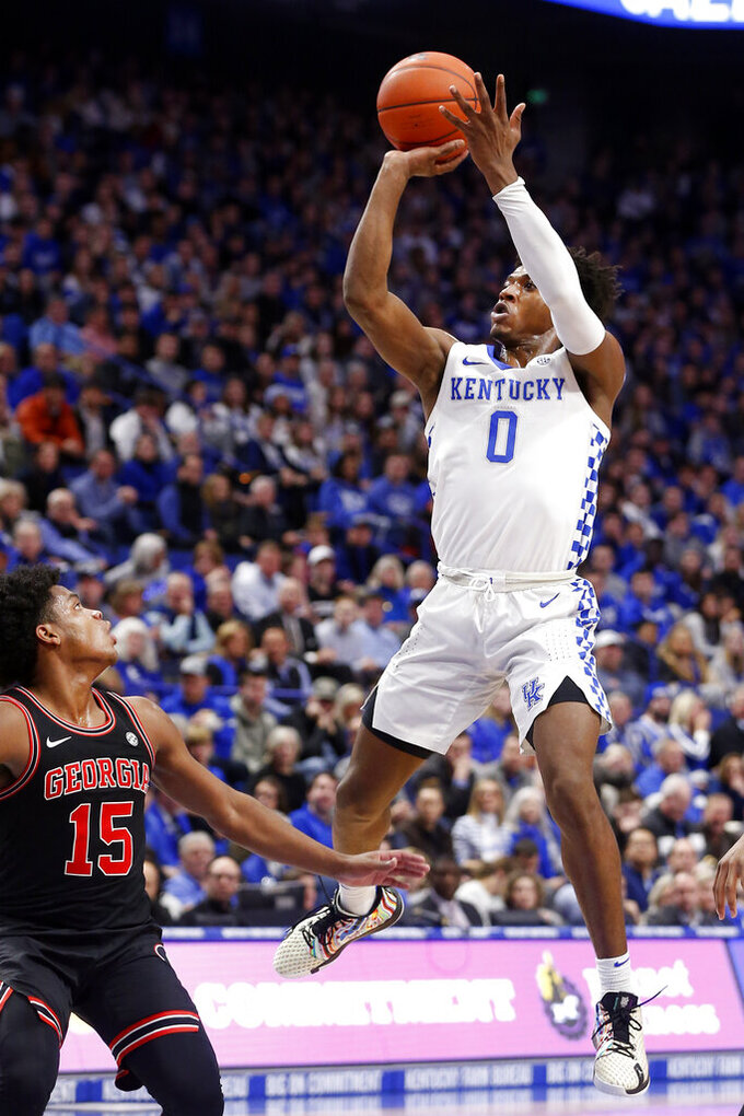 Kentucky's Ashton Hagans (0) shoots near Georgia's Sahvir Wheeler (15) during an NCAA college basketball game in Lexington, Ky., Tuesday, Jan 21, 2020. (AP Photo/James Crisp)