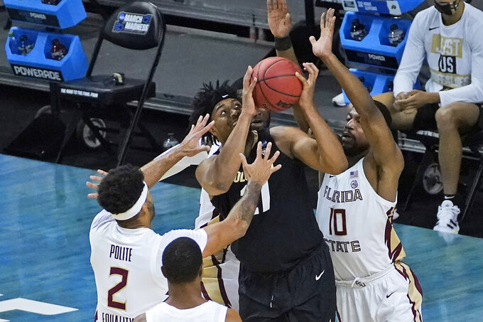 Colorado forward Evan Battey (21) is swarmed by Florida State guard Anthony Polite (2) and teammate Malik Osborne (10) during the second half of a second-round game in the NCAA college basketball tournament at Farmers Coliseum in Indianapolis, Monday, March 22, 2021. (AP Photo/Charles Rex Arbogast)