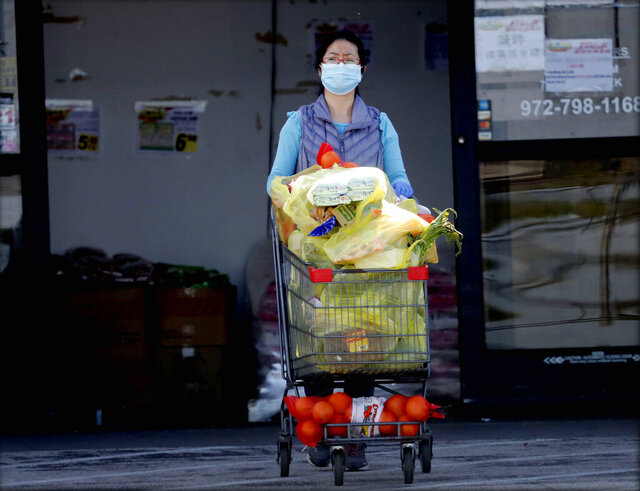 Wearing a mask amid concerns of the spread of COVID-19 a woman pushes a basket full of groceries out of a store in Richardson, Texas, Wednesday, April 1, 2020. (AP Photo/LM Otero)