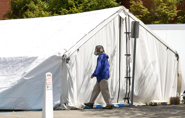 A pedestrian wearing a facemask walks past a tent used for taking coronavirus tests on Tuesday, June 30, 2020, in a parking lot outside Gritman Medical Center in Moscow, Idaho. (Geoff Crimmins/Moscow-Pullman Daily News via AP)