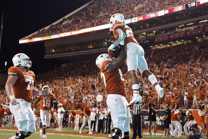 Texas running back Jonathon Brooks (24) is lifted by Tope Imade (67) after his touchdown against Rice during the second half of an NCAA college football game Saturday, Sept. 18, 2021, in Austin, Texas. (AP Photo/Chuck Burton)