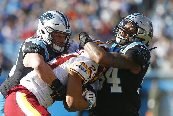 Carolina Panthers middle linebacker Luke Kuechly, left, and outside linebacker Shaq Thompson (54) tackle Washington Redskins running back Derrius Guice (29) during the first half of an NFL football game in Charlotte, N.C., Sunday, Dec. 1, 2019. (AP Photo/Brian Blanco)