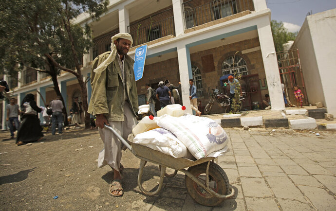 A displaced Yemeni receives food aid provided by the World Food Programme, at a school in Sanaa, Yemen, Sunday, Aug. 25, 2019. The U.N. humanitarian chief in Yemen warned last Wednesday that unless significant new funding is received in the coming weeks, food rations for 12 million people in the war-torn country will be reduced and at least 2.5 million malnourished children will be cut off from life-saving services. (AP Photo/Hani Mohammed)