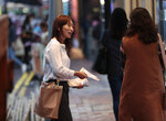 In this photo taken Thursday, Nov. 7, 2019, district council candidate Cathy Yau distributes flyers to pedestrians during her campaign at Causeway Bay in Hong Kong. Yau. a former police officer, grew exasperated as police used more force to quell the unrest. She quit the force in July after 11 years and is running in Sunday's district polls that are widely expected to deliver a decisive victory for the six-month-old movement seeking democratic reforms in the semi-autonomous Chinese territory. (AP Photo/Dita Alangkara)