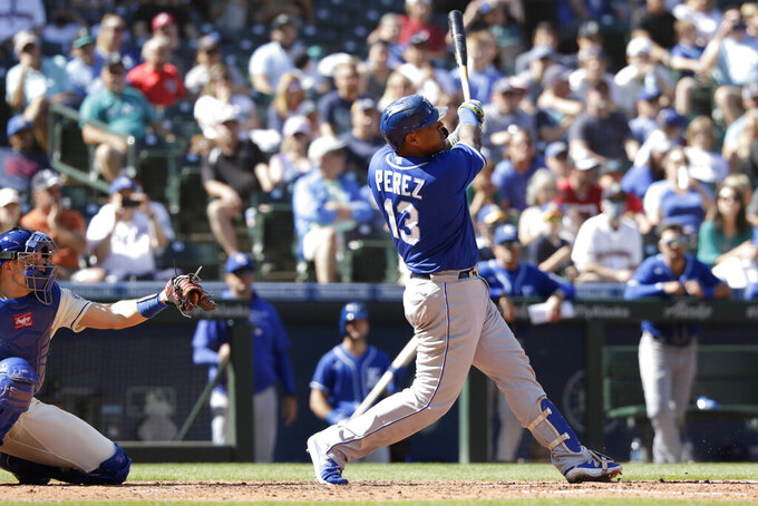 Kansas City Royals' Salvador Perez (13) hits a home run as Seattle Mariners catcher Cal Raleigh, left, looks on during the sixth inning of a baseball game Sunday, Aug. 29, 2021, in Seattle. (AP Photo/Jason Redmond)