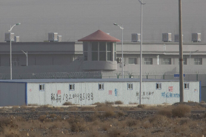 FILE - In this Monday, Dec. 3, 2018, file photo, a guard tower and barbed wire fences are seen around a facility in the Kunshan Industrial Park in Artux in western China's Xinjiang region. The U.S. Customd snd Border Protection on Wednesday said it will block imports from a major Chinese producer of cotton goods for its suspected use of workers detained as part of a crackdown on ethnic minorities in China's northwest. (AP Photo/Ng Han Guan, File)
