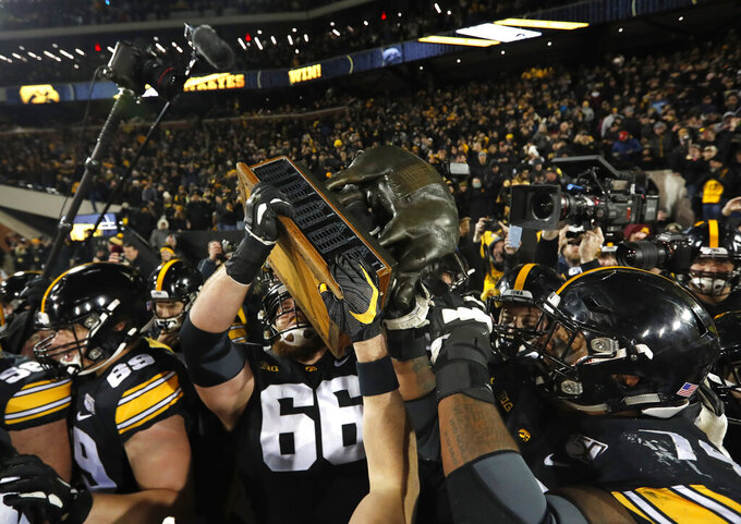 Iowa carries off the Floyd of Rosedale Trophy off the field while surrounded by fans after defeating Minnesota in an NCAA college football game, Saturday, Nov. 16, 2019, in Iowa City, Iowa.(AP Photo/Matthew Putney)