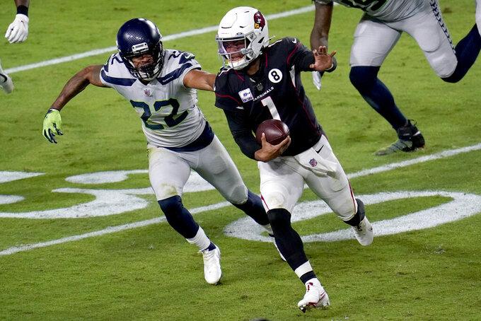 Arizona Cardinals quarterback Kyler Murray (1) eludes the reach of Seattle Seahawks cornerback Quinton Dunbar (22) during the first half of an NFL football game, Sunday, Oct. 25, 2020, in Glendale, Ariz. (AP Photo/Ross D. Franklin)