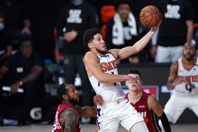 Phoenix Suns' Devin Booker (1) goes to the basket over Miami Heat's Andre Iguodala, left, and Tyler Herro, right, during the second half of an NBA basketball game, Saturday, Aug. 8, 2020, in Lake Buena Vista, Fla. The suns won 119-112. (AP Photo/Ashley Landis, Pool)