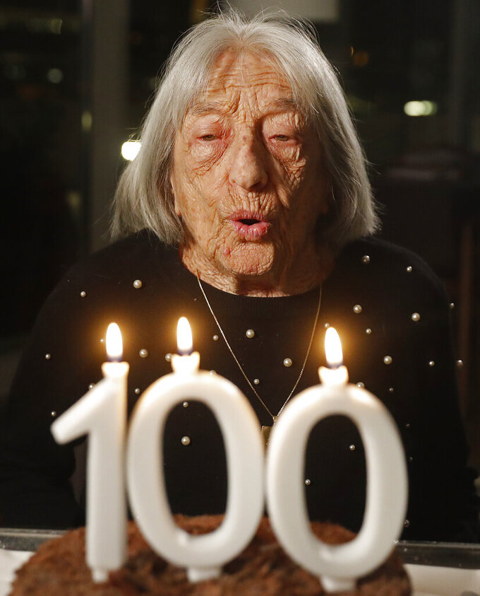 Agnes Keleti, former Olympic gold medal winning gymnast, blows out the candles on her birthday cake in Budapest, Hungary Monday Jan. 4, 2021. The oldest living Olympic champion turns 100 and says the fondest memory of her remarkable life is simply that she has lived through it all. Keleti had her illustrious career interrupted by World War II and the subsequent cancellation of the 1940 and 1944 Olympics. (AP Photo/Laszlo Balogh)