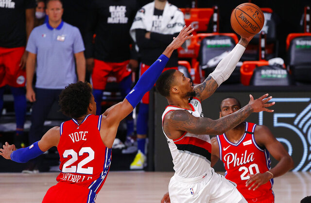 Portland Trail Blazers' Damian Lillard shoots next to Philadelphia 76ers' Matisse Thybulle, left, during the fourth quarter of an NBA basketball game Sunday, Aug. 9, 2020, in Lake Buena Vista, Fla. (Kevin C. Cox/Pool Photo via AP)