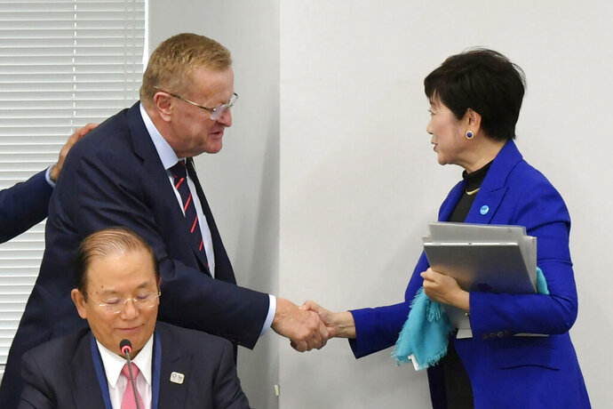 "FILE - In this Wednesday, Oct. 30, 2019, file photo, Tokyo Gov. Yuriko Koike, right, shakes hands with International Olympic Committee member John Coates during their meeting in Tokyo. The IOC abruptly announced two weeks ago it was moving next year's Olympic marathon from Tokyo to the northern city of Sapporo. Coates, who supervises Tokyo preparations, said the decision was made based on ""what we saw in Doha, Qatar."" (Kyodo News via AP)"