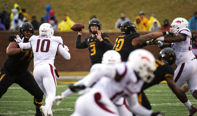 Missouri quarterback Drew Lock, center, throws a pass during the first half of an NCAA college football game against Arkansas, Friday, Nov. 23, 2018, in Columbia, Mo. (AP Photo/L.G. Patterson)